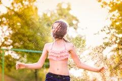 Girl in bikini dancing at the sprinkler, summer garden Royalty Free Stock Photo