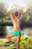 Girl in bikini doing yoga next to a river at sunset Royalty Free Stock Image
