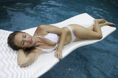 Girl in bikini floating on a raft Stock Photo