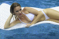 Girl in bikini floating on a raft Royalty Free Stock Photos