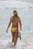 Girl in a bikini with her surfboard Royalty Free Stock Images