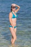 Girl in bikini hids her eyes from sun Stock Images
