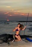 Girl in bikini holding fishing spare. Stock Image