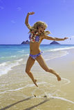 Girl in bikini jumping at the beach Stock Photography