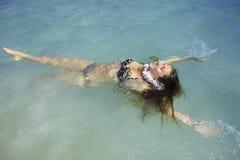 Girl in bikini at lanikai beach. Beautiful girl in bikini floating in the ocean in hawaii Royalty Free Stock Images