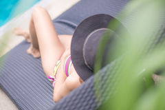Girl in bikini lie down on daybed side pool. Summer Royalty Free Stock Photography