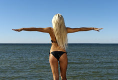 Girl in a bikini looks at the blue sea Royalty Free Stock Photo