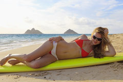 Girl in a bikini lounges on a surfboard