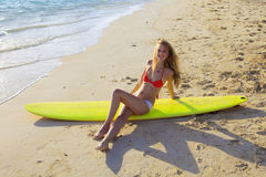 Girl in a bikini lounges on a surfboard Royalty Free Stock Photos