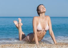 Girl in bikini lying bent back with eyes closed outdoors. Attractive young woman tanning on pebble seashore. Fine girl in bikini lying bent back with eyes closed stock image