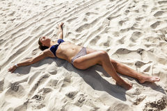 Girl in a bikini lying on the sand at the beach with open hands Royalty Free Stock Photo