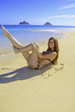 Girl in bikini lying on a sandy beach Royalty Free Stock Photos
