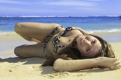 Girl in bikini lying on a sandy beach Stock Photography