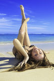 Girl in bikini lying on a sandy beach Royalty Free Stock Photography