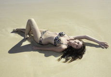 Girl in bikini lying on a sandy beach Stock Image