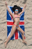 Girl in bikini lying on the Union Flag Stock Photography