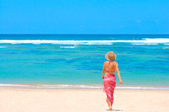 Girl in bikini and pareo walking towards ocean Stock Photo