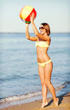Girl in bikini playing ball on the beach Stock Photos