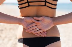 Girl in bikini posing with her hands behind her back Stock Images