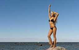 Girl in bikini posing on a rock near the sea Royalty Free Stock Photo