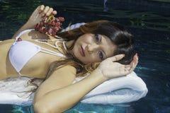 Girl in bikini on a raft in a pool Stock Image