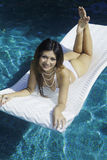 Girl in bikini on a raft in a pool Stock Photo