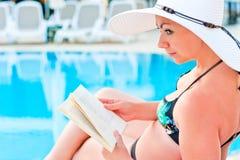 Girl in bikini reading a book near the pool Stock Photo