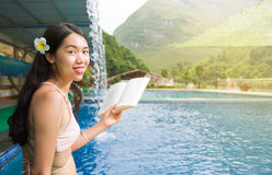 Girl in bikini reading a book by the pool Royalty Free Stock Images