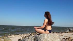 Girl in bikini relaxing on stone stock video