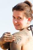 Girl in a bikini rubs mud Stock Photos