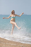 Girl in bikini running along seashore. She splashes and shouts Royalty Free Stock Images