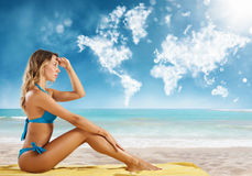 Girl in bikini sits on a beach looking for new travel destination. Royalty Free Stock Image