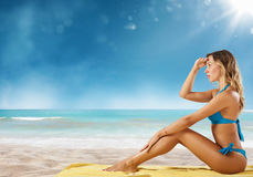 Girl in bikini sits on a beach looking for new travel destination. Royalty Free Stock Photos
