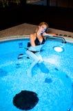 Girl in bikini sits in hot water in whirlpool tube Stock Photos
