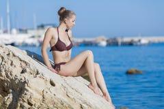 Girl in bikini sits on rock and looks on sea Stock Image