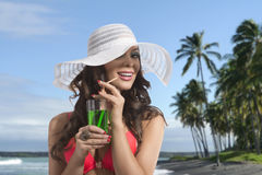 Girl in bikini smiles and drinking on palm beach Stock Photography