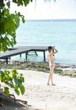 Girl in bikini standing on the beach Stock Images