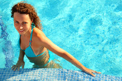 Girl in bikini stands in swimming-pool. Smiling girl in blue bikini with brown curly hair stands in swimming-pool Royalty Free Stock Images