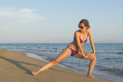 Girl in bikini stretching and exercising at the beach Royalty Free Stock Photos