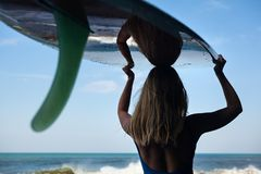 Young woman with surfboard walk on black sand beach. Girl in bikini with surfboard walk on black sand beach. Surfer woman look at sea surf and water pool with Royalty Free Stock Photography