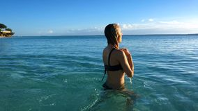 A girl in a bikini swims in the Indian Ocean at sunset ona lonely tropical beach. A girl in a bikini swims in the clear Indian Ocean at sunset near a beautiful stock video