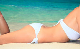 Girl in bikini tanning in the bright summer sun. Royalty Free Stock Photos