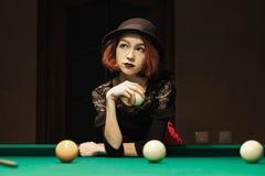 Girl in the billiard room. Beautiful girl in a hat in the billiard room Stock Image