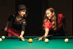 Girl in the billiard room. Two beautiful girls in the billiard room Royalty Free Stock Photography