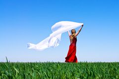 Girl with billowing white. Cloth runs on green field Royalty Free Stock Photography