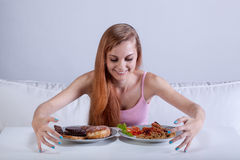 Girl binging on lots of food. Young skinny girl binging on lots of food Royalty Free Stock Images