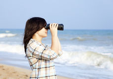 Girl with binocular at the beach Royalty Free Stock Photo