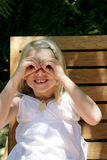 Girl with binocular hands. Young blonde girl holding her hands over her eyes like a pair of binoculars, caucasian/white Stock Photography