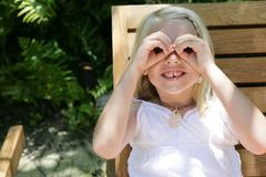 Girl with binocular hands. Young blonde girl holding her hands over her eyes like a pair of binoculars, caucasian/white Royalty Free Stock Photography