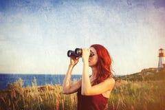 Girl with binocular near Lighthouse Stock Images
